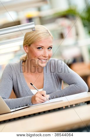 Female student working on the laptop sitting at the table. Process of studying