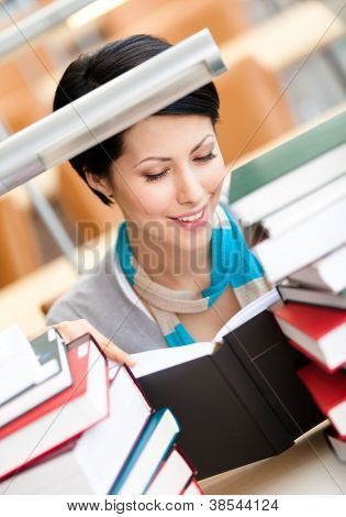 Reading book female student surrounded with piles of books sitting at the desk at the library. Knowledge concept