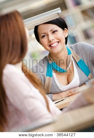 Two girls communicate sitting at the desk at the reading hall. Communication concept