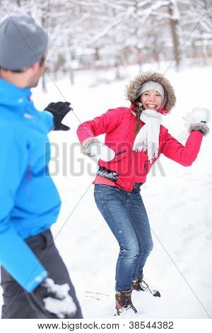 Young couple playing in the snow in snowball fight with a vivacious smiling Asian girl taking aim at her husband with a snowball