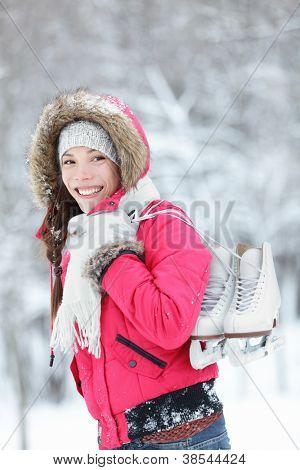 Schöne junge asiatische Frau, die gerne als She-Spaziergänge durch die winterliche Landschaft mit ihrem Lächeln ice sk