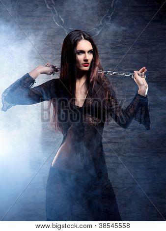 Conceito de Halloween: jovem e sexy bruxa na masmorra