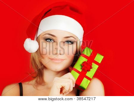 Happy Santa girl holding colorful Christmas gift, Christmastime fun and joy, celebration of winter holidays, on red background