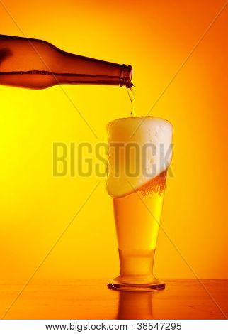 Waiter pouring beer, glass of a cold drink isolated on yellow warm background, festival of beer, Oktoberfest autumn holiday