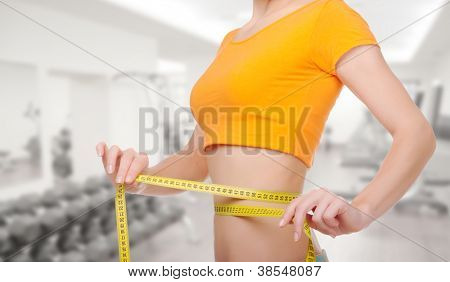 Young sporty woman with centimeter tape