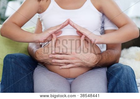 Future parent making home shaped on stomach pregnant woman, family house concept