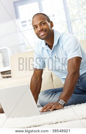 Porträt von glücklich hübscher Afro Mann mit Laptop-Computer zu Hause auf dem Boden.