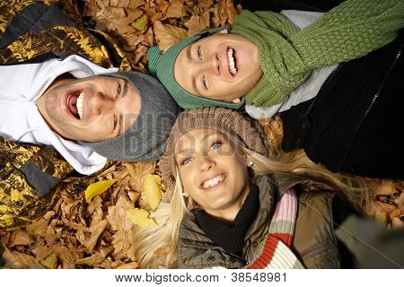 Attractive young people laying on ground among autumn leaves, smiling, having fun.