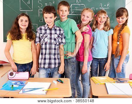 Grupo de la escuela niño sentado en el escritorio en el aula.