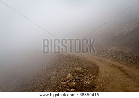 Himalayas. Gravel mountain road in the fog.