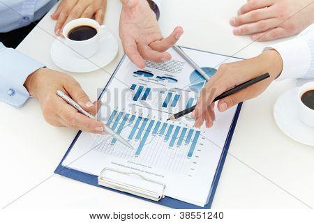 Imagen de manos humanas con plumas sobre documento de negocio en reunión