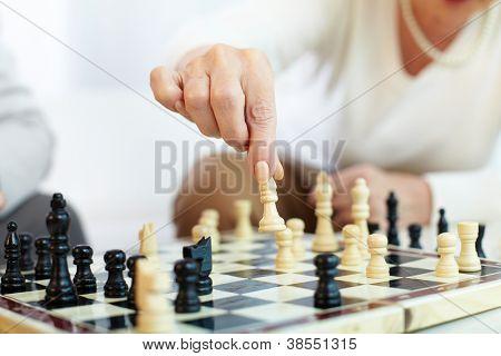 Portrait of senior human hand holding chess figure