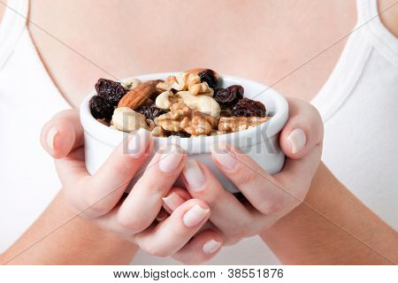 Close-up of woman holding bowl of dry fruits.