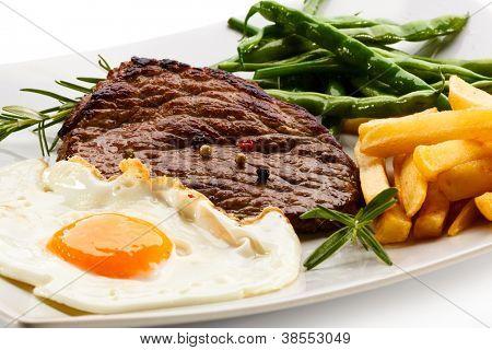 烤的牛排、 薯条、 煎的鸡蛋和蔬菜