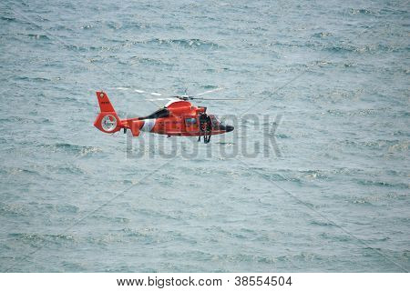 ATLANTIC CITY, NJ - AUGUST 24: US Coast Guard HH-65A Dolphin helicopter drops rescue diver during rescue exercise August 24, 2011 in Atlantic City, New Jersey