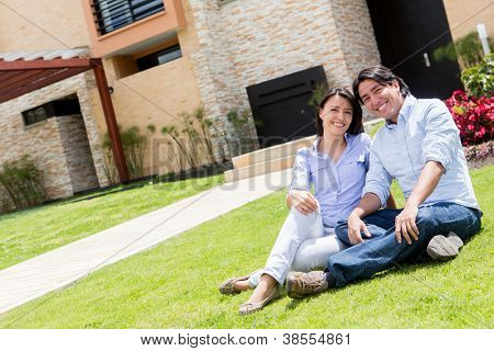 Happy couple sitting outdoors in the front yard