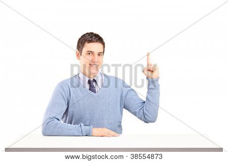 A smiling man sitting on a table and pointing with his finger isolated on white background