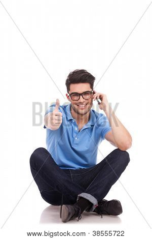 Appealing casual young man sitting with his legs crossed and showing thumbs up sign, while speaking on the phone and smiling. Isolated on white background
