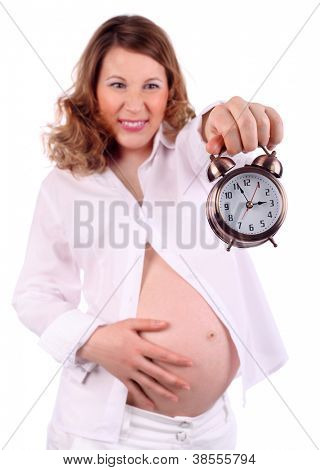 Dissatisfied pregnant woman in white holds at arm alarm clock and touches belly isolated on white background. Focus on clock.