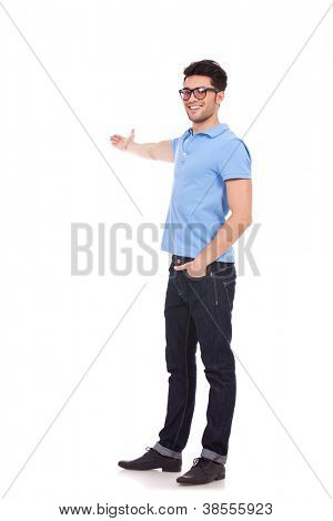 Full body picture of a happy young casual man presenting something in the back with a hand in pocket and looking at the camera