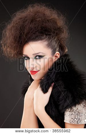 Portrait of young fashion woman with extravagant hairstyle and make-up, holding her black fluffy vest, on a dark background