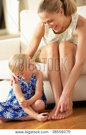 Daughter Painting Mother's Toenails At Home