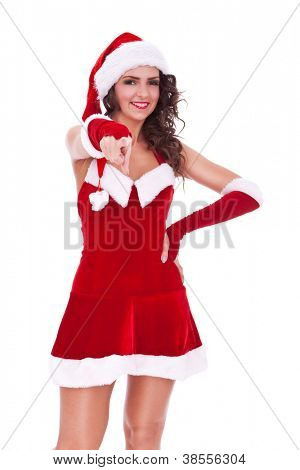 gorgeous young woman in christmas costume pointing and holding a hand on her hip while looking at the camera with a smile on her face