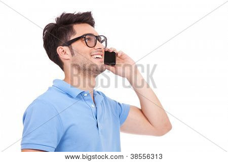 side view portrait of a casual young man speaking on the phone and smiling while looking away, somewhere up. on white background