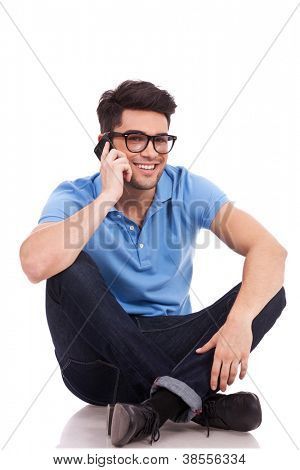 Portrait of a sitting casual young man who is speaking on the phone and smiling to the camera