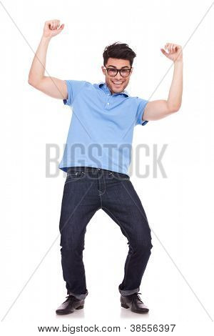happy young casual man celebrating, cheering with both his arms in the air,  isolated over a white background