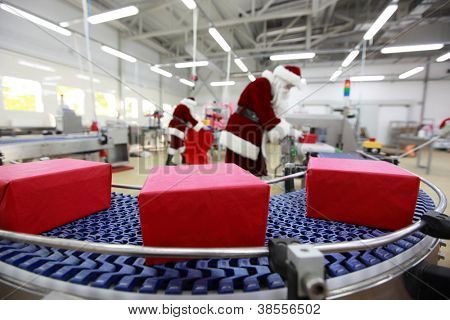 Two Santa Clauses working in Xmas Gifts Factory