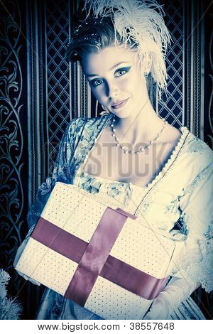 Portrait of the elegant woman posing with Christmas present over vintage background.