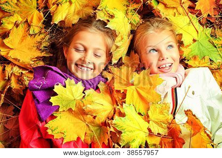 Portrait of two cute girls sisters posing at the autumn park.