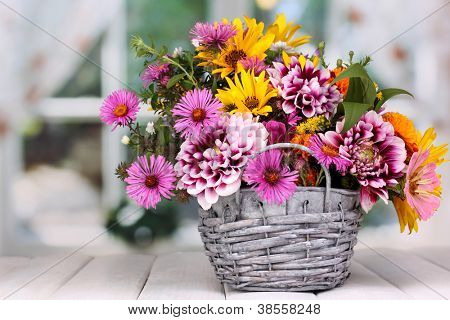 beautiful bouquet of bright flowers in basket on wooden table