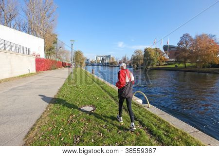 BERLIN, GERMANY - NOVEMBER 3: Man runs along river Spree on November 3, 2011 in Berlin, Germany. River Spree is approximately 400 kilometres (250 mi) in length.