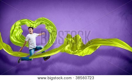 Young man dancing with green fabric over purple background