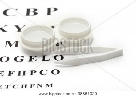 contact lenses in containers and tweezers, , on snellen eye chart background