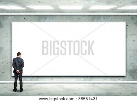 Business person standing near a white blank  billboard