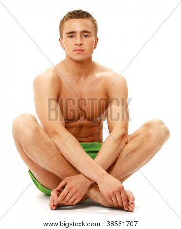 Muscular male model in swimwear sitting on the floor, isolated on white background