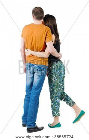 Back view of young couple (man and woman) hug and look. Rear view. Isolated over white background. The man in the orange T-shirt and jeans, woman in green pants and a black T-shirt