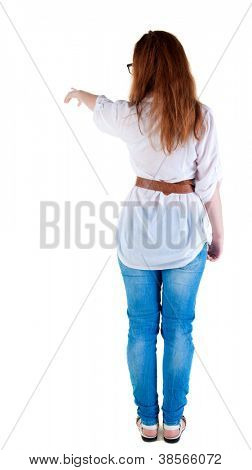 back view of pointing beautiful redhaired  woman . Young girl in  jeans.  Rear view people collection.  backside view of person.  Isolated over white background.
