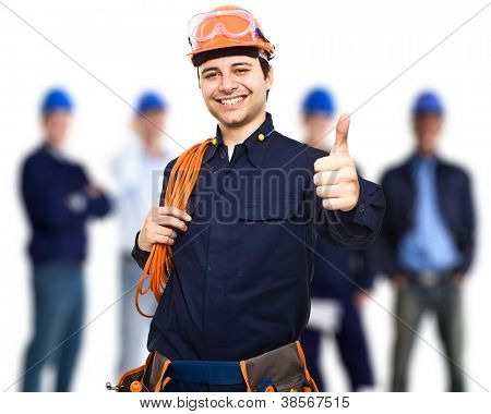 Retrato de un trabajador feliz frente a su equipo
