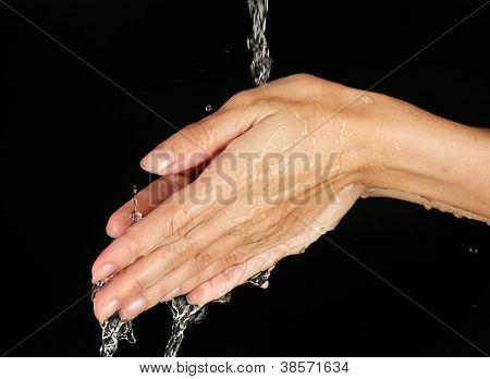 Washing hands on black background close-up