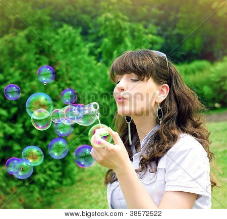 romantic young girl inflating colorful soap bubbles in spring park