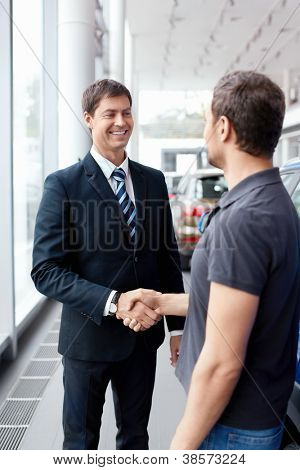Buyer and seller shake hands in the auto show
