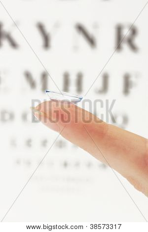 contact lens on finger, on snellen eye chart background