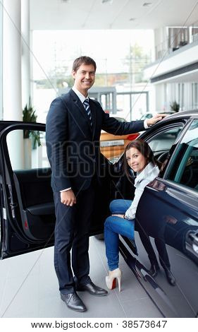 Woman in the car and seller at a showroom