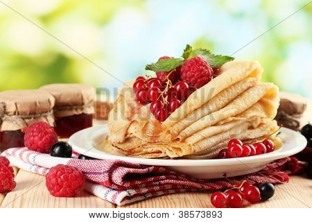 pancakes with berries, jam and honey on wooden table on  green background