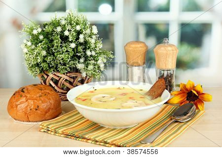 Fragrant soup in white plate on table on window background close-up