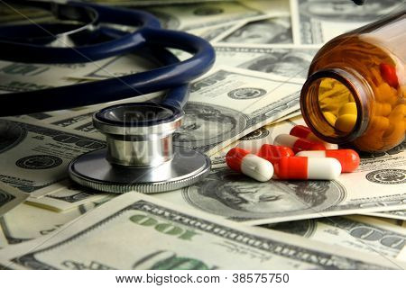 A medical stethoscope and pills on dollars